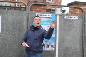 Le photographe prend le smartphone qui prend en photo le candidat devant les photos de son affiche.